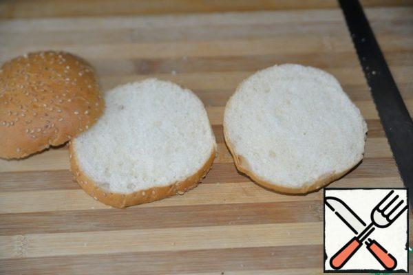 We take a hamburger bun, I have a ready-made one with sesame seeds. With a knife (preferably with a file), cut lengthwise into three equal parts.