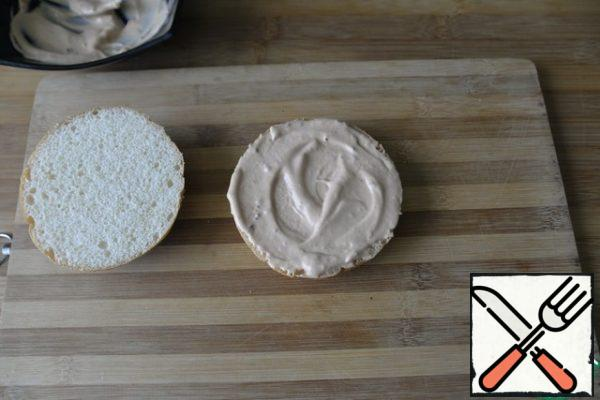 It is better to collect the Burger immediately before use, so as not to get wet. We take a hamburger bun: ready-made or self-made. I have ready with sesame seeds, cut with a knife, better with a file in half. Lubricate the lower part liberally with sauce.