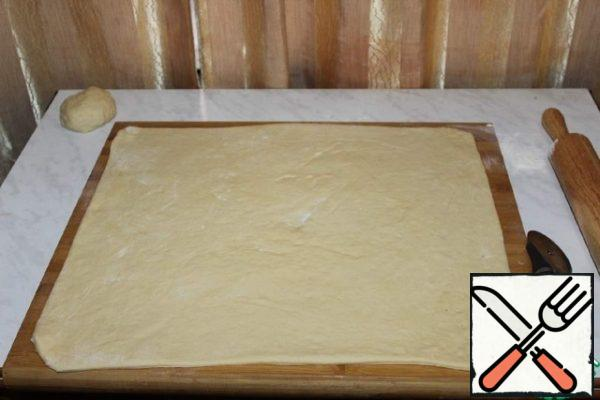 Roll out into a rectangular layer. And grease with butter.