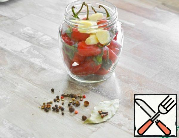 The calculation of products is given for a half-liter jar. Wash and sterilize the jar. Wash the lid and boil it. At the time of canning, the lid should be hot (keep it in boiled hot water)I have 15 peppercorns in my jar. Lay it tightly, but do not tamper, so that the peppercorns do not burst. Add the chopped garlic, Bay leaf, a couple of whole cloves and pepper to the jar. I have a mixture of 5 peppers, you can take any peas.