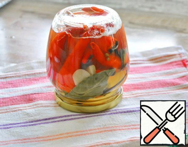 """Pour the boiling marinade over the peppers in the jar, screw the hot boiled lid on. Turn it over on a towel and wrap it up until it cools down. After cooling, make sure that the lid is """"sucked in"""" - it is concave inside.The pepper will be marinated for about a month. The jar preserved in this way can be stored in the room. After opening the jar, it will need to be stored in the refrigerator."""