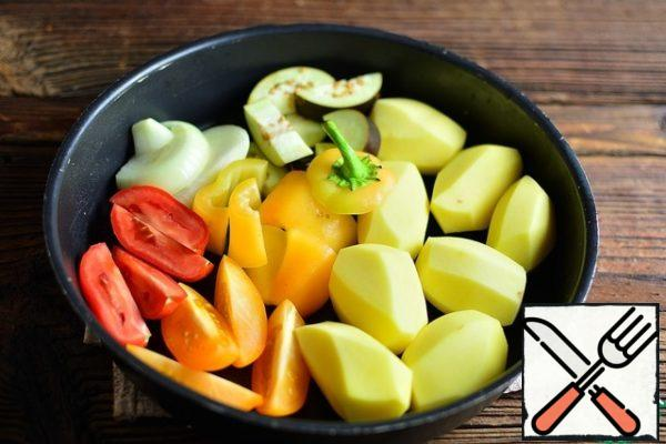 Peel the potatoes, tomatoes, onions, eggplant and pepper and chop them coarsely. Put all the vegetables in a baking dish.