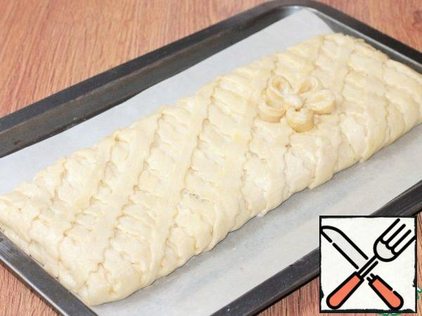Coat the baking pan with baking paper and grease with butter. Transfer the pie to paper. Mix the melted butter (3 tbsp) with liquid sour cream (1 tbsp) and grease the pie. Put the baking sheet in the oven and turn on the minimum temperature of 40 C.