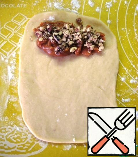 Roll out a piece of dough. Put the boiled condensed milk and chopped nuts on the edge (about 1 tsp each).