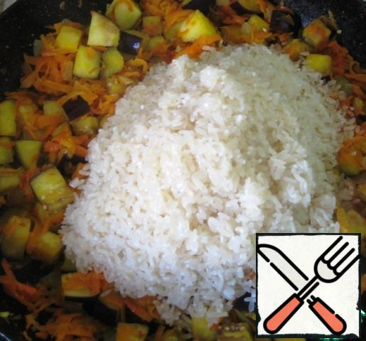 As soon as the eggplant changes color and becomes slightly soft, add the well-washed rice, removing the water as much as possible. Mix thoroughly. Continue to fry the rice and vegetables, stirring every 2-3 minutes. Rice should become dry, amber.