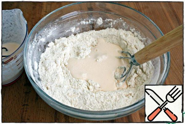 Add kefir to the flour in parts and knead the dough with a whisk (spoon).