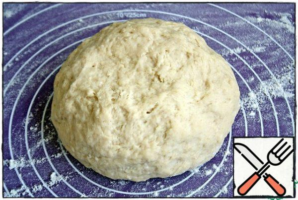 After ten minutes, put the dough on the work surface, dusted with flour and roll out into a rectangular layer measuring thirty by forty centimeters. If the rolling pin will stick to the dough, then the dough is also slightly dusted with flour, just a little- do not overdo it.