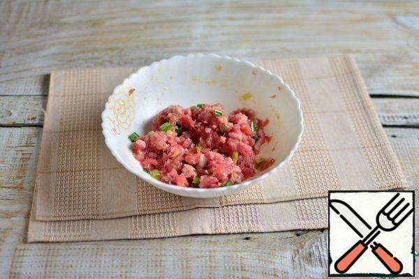 Cut off excess fat from the lamb, turn it in a meat grinder with a large grate, add garlic through a press (1 clove), egg, chopped green onions, egg, spices for lamb and salt to taste. Stir.