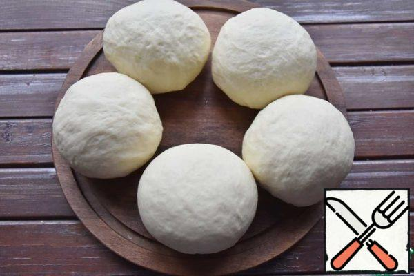 I got five rolls, weighing 115 grams. You can make them smaller. Roll each part of the dough into a ball, put it on a Board and cover with a film or napkin. Leave for another 30 minutes.