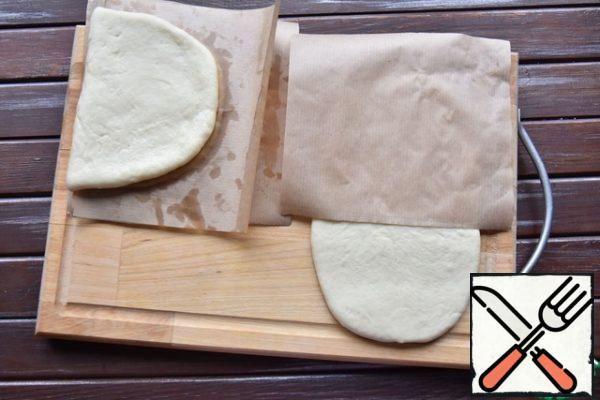 Put the paper blank on half of the dough and roll the tortilla in half, covering the paper on top.