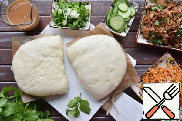 For the sauce, mix and warm the peanut paste with soy sauce and water. Stir the sauce until smooth and pour into a saucepan. Assemble all the components to build gua Bao.