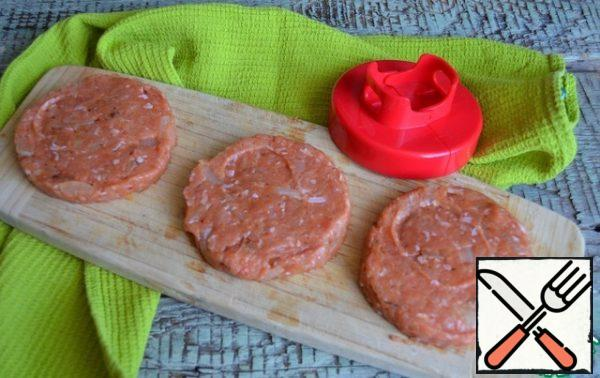 Beat off the minced meat, form three flat cutlets, slightly larger than the diameter of the buns.