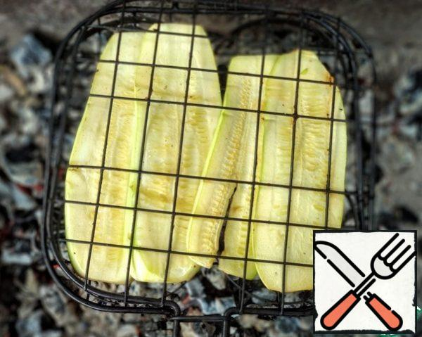 Wash the zucchini and peel it. Cut into plates, brush them with olive oil and salt. Spread on the grill and fry on the grill.