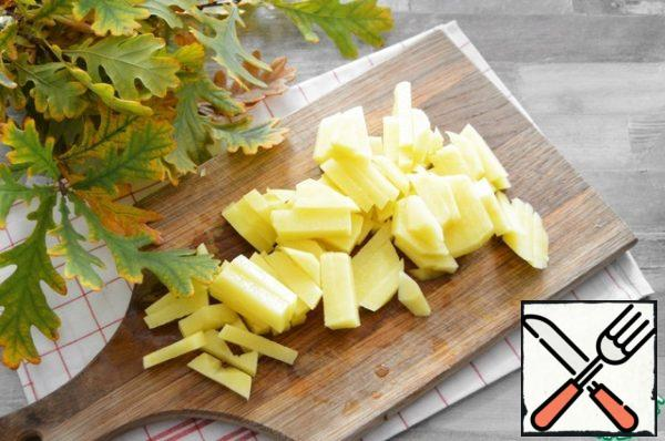 Peel the potatoes and cut them into cubes.