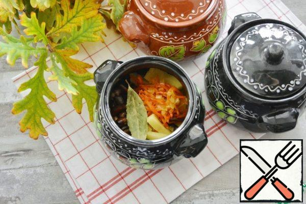 Put the sliced potatoes, honey mushrooms and fried onions and carrots in pots. In each pot put a Bay leaf and a little salt to taste.