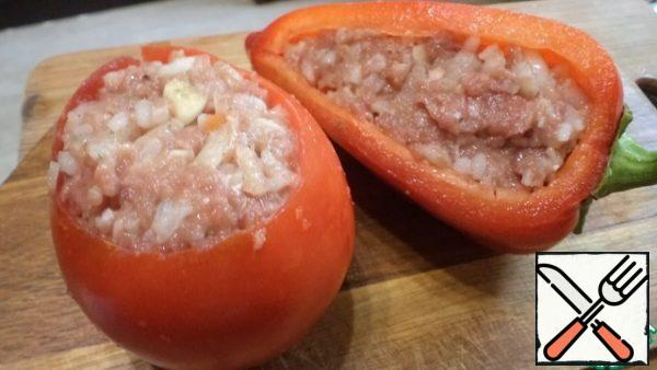 Fill the vegetables with minced meat and put them in a saucepan with butter. At the bottom of the saucepan before this, put the insides of the tomato. Pour 1/2 Cup of water and put it to stew for 30-40 minutes. depending on the size of the peppers and tomatoes. Add water as needed.