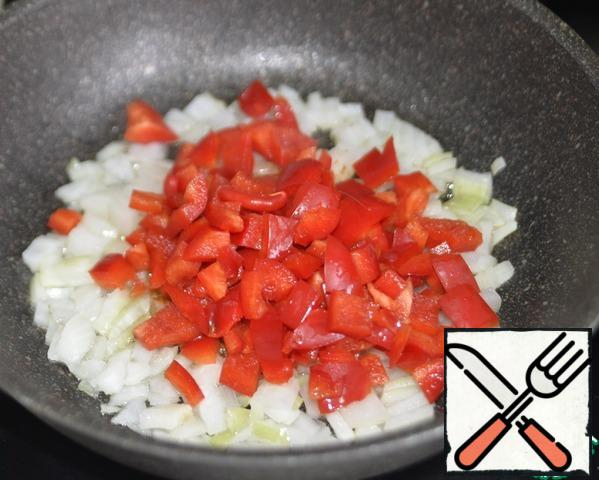 Wash pepper, clean, cut into cubes, put it to the onion, simmer over medium heat for 5 minutes.