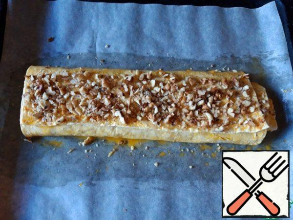 Top the roll with egg yolk and sprinkle with chopped walnuts. Bake in the oven for about 10 minutes at 180 degrees. Serve the roll with tea or coffee.