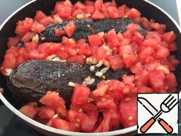 Put our eggplant and pepper in the pan (you can use the one where the vegetables were fried, if the oil is not burned out), top with tomatoes and garlic, salt.