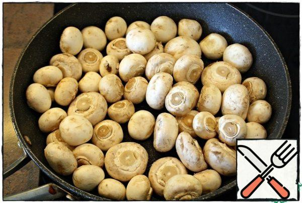 First of all, heat a dry frying pan well over high heat, then reduce the heat to just below average, spread the mushrooms, cover with a lid. When a large amount of liquid is released from the mushrooms, remove the lid and evaporate.
