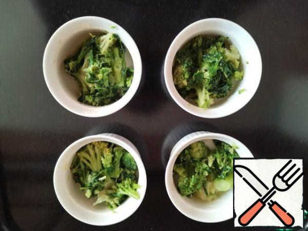 Preheat the oven to 150°C. Grease 4 200 ml baking pans with oil. Break the broccoli into inflorescences, cut the stem into small pieces, and put it in molds.