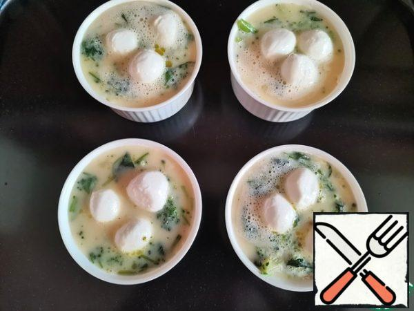 Beat eggs with salt, pepper, milk and semolina. And pour into the molds on top of the broccoli and spinach. Slice the mozzarella (or grate it) and sprinkle it on top.