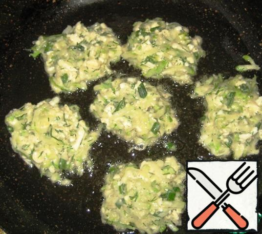 Heat the vegetable oil in a frying pan, add the zucchini pancakes with a tablespoon and fry over medium heat until Golden brown.