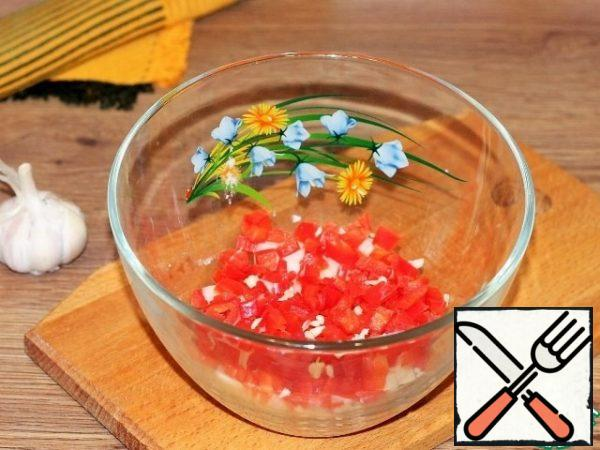 Red pepper is peeled from the seeds and tail and finely chopped. Add the pressed garlic.