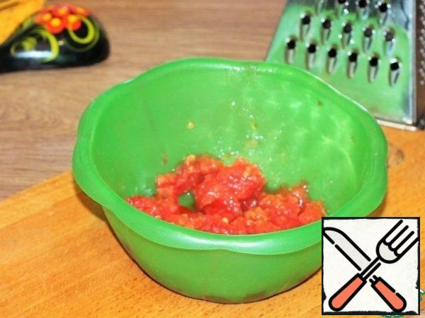 The second tomato is grated on a large grater, the skin is removed.