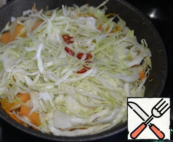 Put the cabbage in the pan, add the hot pepper cut into rings.
