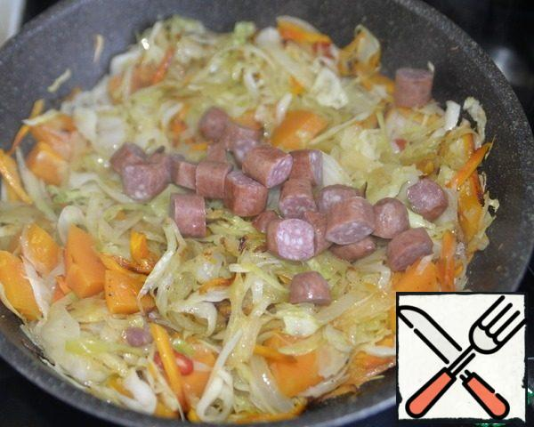 Put the chopped Hunting sausages, mix, and fry for 3 minutes. I'm at this stage slightly increase the heat to evaporate the excess liquid, but constantly interfere so that the vegetables do not burn.
