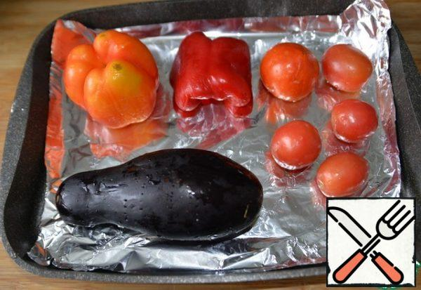 We take vegetables in a ratio of 1:1:1. Wash. Put foil on a baking sheet, eggplant, peppers, tomatoes on it. We pierce the eggplant with a fork several times. Put in the oven at 200 degrees for 40 minutes.