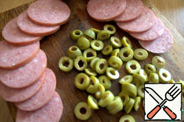 For the filling, cut any sausage (I have Servelat) and olives into rings.