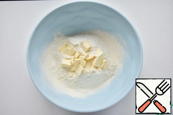 Mix flour with baking powder and sift through a sieve. Add the cold butter chopped with a knife or grated on a grater.
