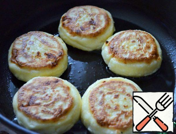 Preheat a frying pan with vegetable oil and 1 tablespoon of melted butter, fry the cheesecakes for 2 minutes on each side, medium heat.