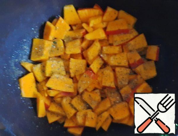 Grease the form with vegetable oil, put the pumpkin, sprinkle with dried herbs and garlic powder, put in a preheated oven for 15 minutes.