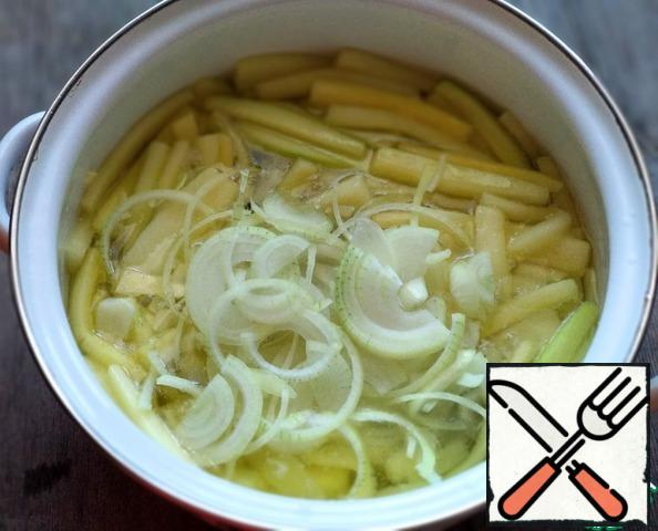 Peel the onion, wash it, and cut it into half rings. Add to the zucchini.