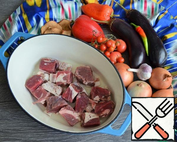 Heat the cumin in a dry pan, this will enhance its flavor in the finished dish, grind it in a mortar. pour vegetable oil into the bottom of the cauldron. Cut the fat lamb and spread it on the bottom of the cauldron. Wash the meat, dry it, cut it into large pieces, add it to the cauldron, add salt and pepper, and sprinkle with cumin.