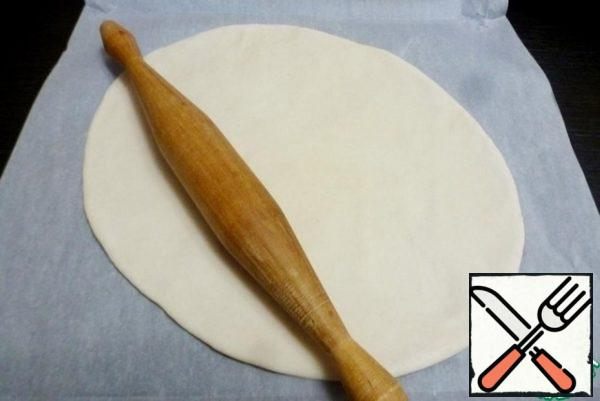 Roll out the dough into a thin tortilla, similar to pizza. I roll it out on baking paper, don't grease it with anything.