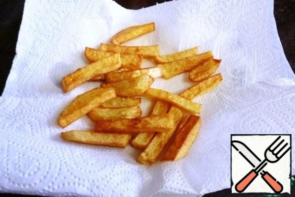 Peel the potatoes and cut them into thin slices. Fry in oil until crisp, in other words, cook French fries. Put on a napkin to get rid of excess oil.