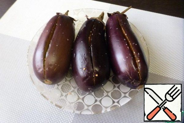 Wash and dry the eggplant, do not trim the tail. Cut the eggplant lengthwise on one side without cutting through. Inside, sprinkle with sugar, salt and leave for 30-40 minutes. During this time, the eggplant pulp will become soft and the juice will stand out. Press the pulp inside, forming a pocket.