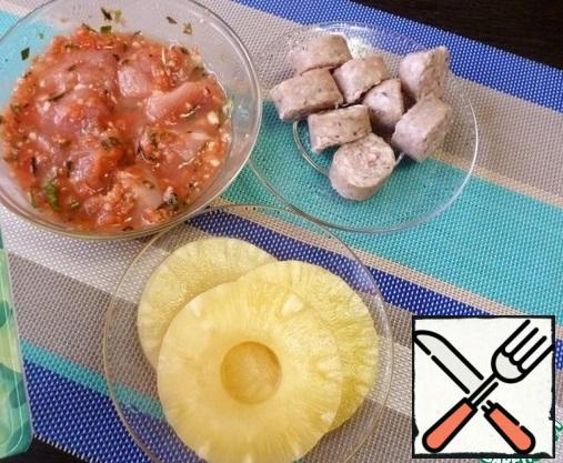 Prepare the ingredients for the kebabs. Sausages for frying cut into rings 1.5-2 cm thick. Cut the pineapples into suitable sized pieces.