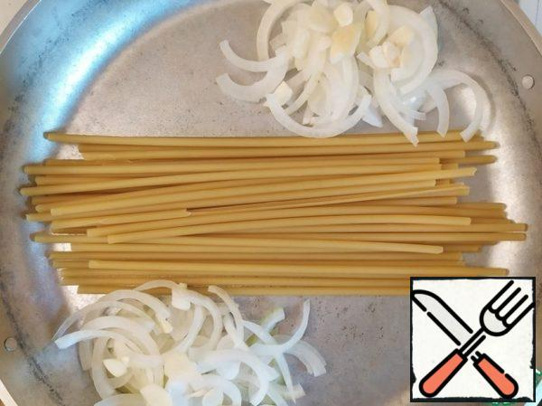 In the pan, put the spaghetti, the sides of the onion cut into half rings and finely chopped garlic.