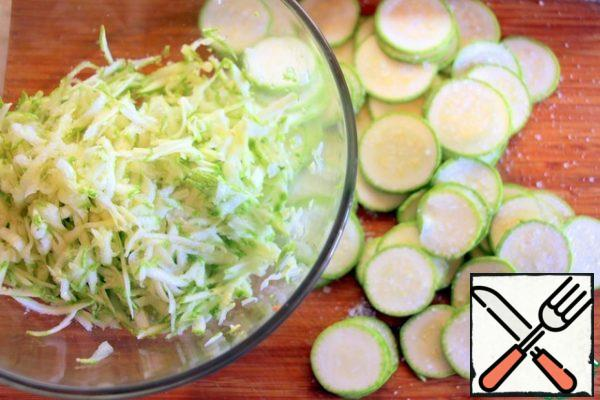 Grate more than half of the zucchini on a coarse grater, cut the rest into slices, add salt and leave for 10 minutes.