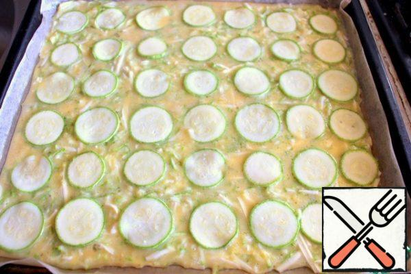 From parchment paper in a 30x40 cm baking sheet, form a form with sides, grease with vegetable oil and pour out the zucchini dough. Put slices of zucchini on top. Bake at 180 degrees for about 20 minutes. The finished cake is turned over on a clean parchment, so that the zucchini circles are at the bottom, remove the parchment, cool.