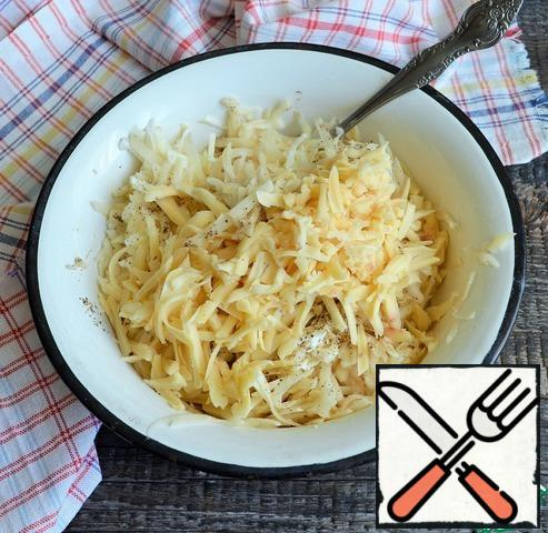 Wash the potatoes, peel them, and grate them on a coarse grater. Add fried onions, 1 tbsp sour cream, grated cheese, salt and pepper to the potatoes and mix.