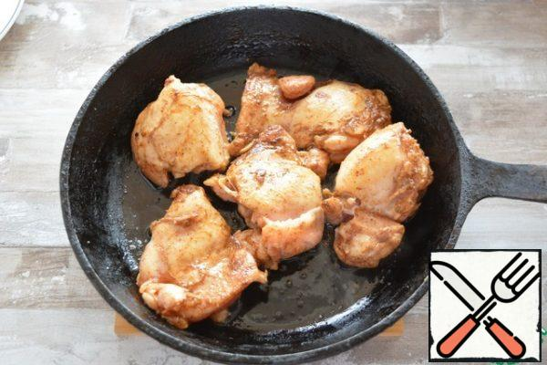 Heat the oil in a cast iron skillet.  Sear the chicken pieces quickly on both sides.  You don't need to cook it, you just need a golden brown crust.  Remove the chicken from the pan onto a plate and set aside for now.
