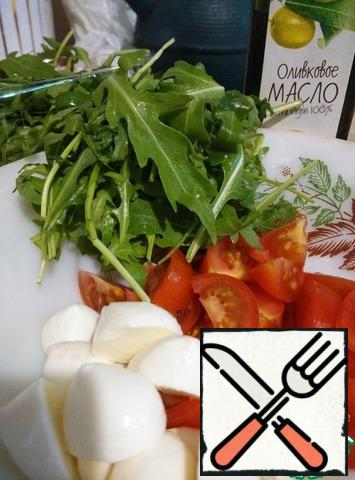 Wash the cherry tomatoes and cut them into 4-6 pieces. Cut the mozzarella balls in half. Wash and dry the arugula.