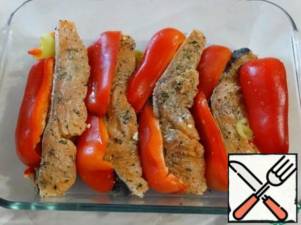 The form is greased with olive oil, put the fish, pour the remaining sauce. Put quarters of sweet pepper between the fish.