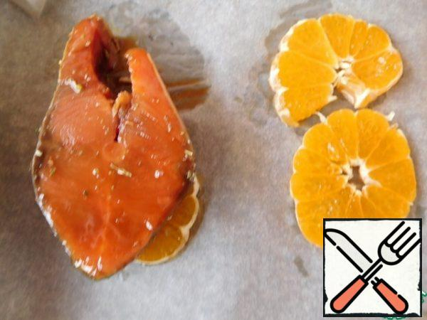 Cut the tangerine into small circles. Place on a baking sheet. Put the fish on top and pour the remaining marinade over it.